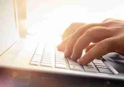 Man's hands typing on laptop keyboard