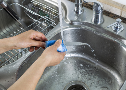 Female hands washing single small knife in kitchen sink