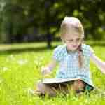 girl reading on grass