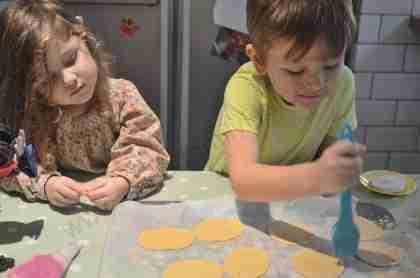 Anna watches while Joseph brushes egg white onto each ravioli circle