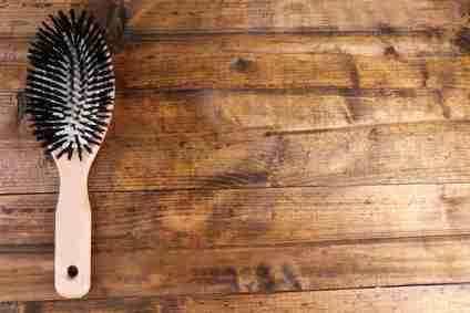 Wooden hairbrush on wooden background